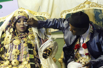A groom wipes the face of his bride during a mass wedding ceremony at an area in Bab al-Aziziyah compound in Tripol