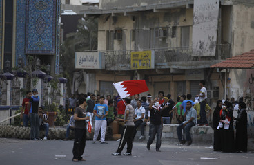 Demonstrators, one waving a Bahraini flag, are seen during a protest in the village of Diraz, west of Manama