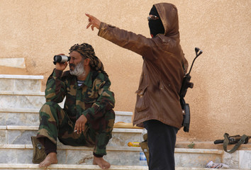 A rebel fighter looks through his scope alongside a fellow fighter after hearing nearby bombardment at the Dehiba border crossing of southern Libya and Tunisia