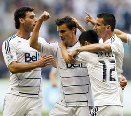 Whitecaps' Rochat celebrates his goal against the Sounders with teammates during the first half of their MLS soccer game in Vancouver