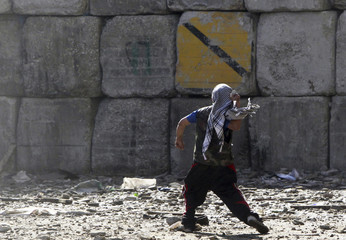 A protester throws a stone at army soldiers at cabinet offices near Tahrir Square in Cairo