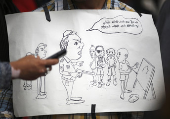 A sign with cartoons is seen during a protest demanding the safety of artist Manish Harijan and his freedom of expression in Kathmandu