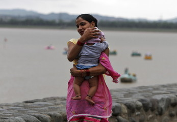 A woman tries to protect her child from a rain shower in Chandigarh