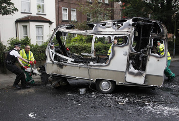 A police officer helps council workers to move the burned out shell of a camper, which was torched during overnight rioting and looting in the neighbourhood of Toxteth in Liverpool