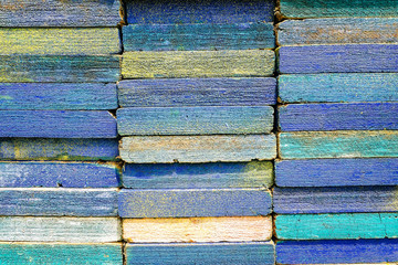 Stack of square wood planks for furniture materials and scaffolding with color paint for background.