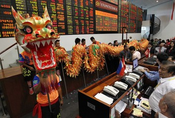 Traders look at traditional dragon dance during Chinese New Year celebrations inside the trading floor of the Philippine Stock Exchange at financial district of Makati city
