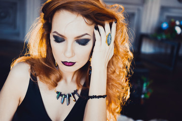 close-up portrait of young beautiful red-haired girl in the image of a Gothic witch on Halloween on a background of wax candles, fire, magic crystals and stones in the black dress conjures