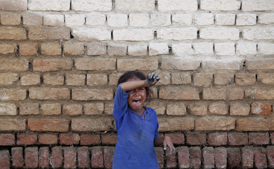 A girl, who has been displaced by floods, cries as she stands beside a wall with floodwaters stain marks while returning with her family to her village of Bello Patan