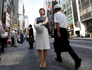 People wearing and holding helmets take part in a drill simulating a 7.2 magnitude earthquake in Tokyo