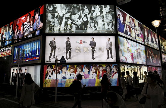 """Passersby are silhouetted in front of an illuminated advertising board of a gigolo club called """"host club"""" in Kabukicho, Tokyo's biggest amusement district"""