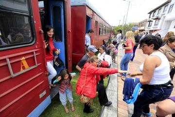 Passengers and tourists alight from a 'La Sabana' tourist train in Zipaquira city