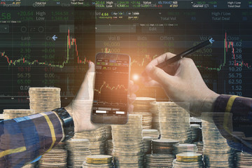Double exposure of Hand holding blank smart phone checking financial stats on screen with group of coins and stock background for trading stock