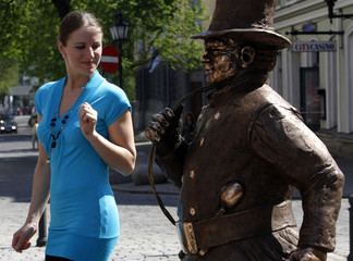 A woman looks at a statue of a chimney sweeper in Tallinn