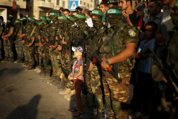 Palestinian boy stands between Hamas militants as they take part in an anti-Israel military parade in Gaza