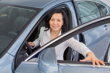 Beautiful mature woman checking out new cars at the dealership
