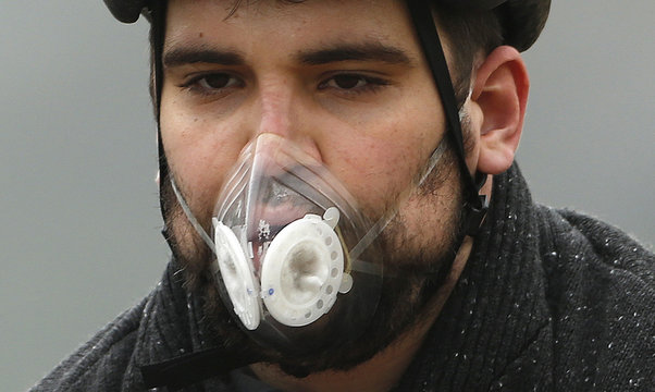 A cyclist wears a mask with an air filter as he cycles through Hyde Park in London