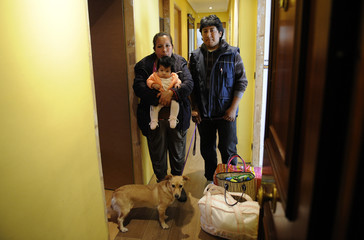 Ecuadoreans Jorge Cordero and Patricia Ordonez pose with their baby at the entrance of their house as they wait to be evicted in Oviedo