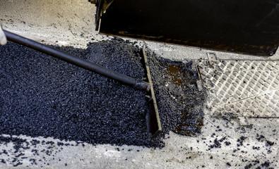 worker leveling fresh asphalt during asphalt pavement repair or construction works