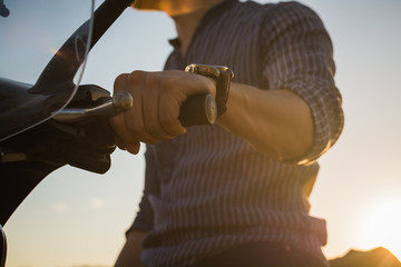 Close up of a man holding steering wheel of a motorcycle