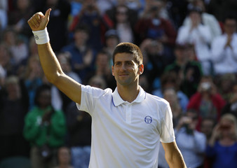 Novak Djokovic of Serbia waves after defeating Jeremy Chardy of France at the Wimbledon tennis championships in London