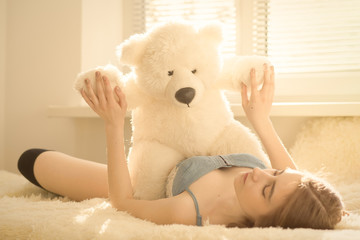 girl embracing with teddy bear in sun light, toned image