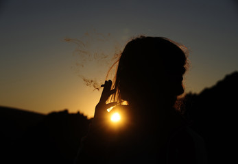 A girl smokes a cigarette during the summer solstice at the Kokino megalithic observatory,