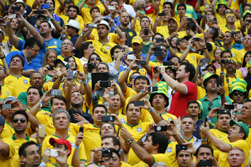 Brazil supporters take pictures before the start of their 2014 World Cup Group A soccer match against Cameroon at the Brasilia national stadium in Brasilia