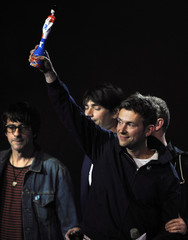 Damon Albarn of Blur holds up their award for outstanding contribution during the BRIT Music Awards at the O2 Arena in London