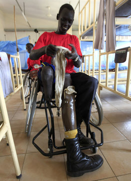 A patient fits a prosthesis inside the men's dormitory at the PRRC in Juba