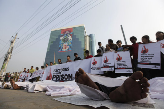 Activists of Magic Movement lie on the ground wearing traditional Muslim death robes as they stage a protest in front of Bangladesh Garment Manufacturers and Exporters Association building in Dhaka