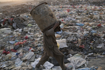 A young garbage collector covers his face with a barrel at a garbage dump on the outskirts of Kabul