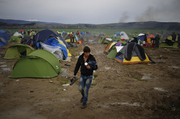 A migrant walks among tents in a makeshift camp on the Greek-Macedonian border near the village of Idomeni