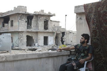 A Free Syrian Army fighter sits on a chair as he smokes a cigarette in Aleppo's Karm al-Jabal district