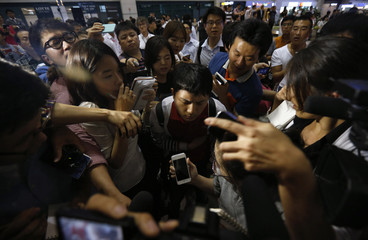 An Asiana flight 214 passenger is surrounded by media after arriving at Incheon International Airport