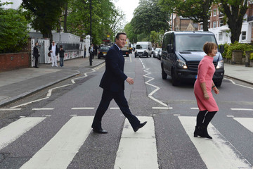 Britain's Prime Minister David Cameron walks accross the pedestrian crossing outside Abbey Road studios with former minister Tessa Jowell (R) in London