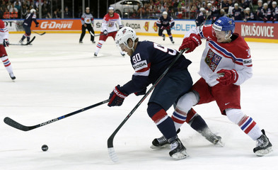 Lee of the U.S. fights for the puck with Krejcik of the Czech Republic during their Ice Hockey World Championship third-place game at the O2 arena in Prague