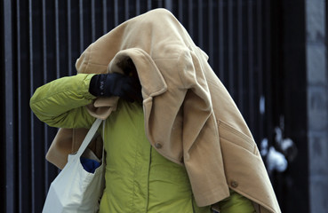 A woman covers her head with a jacket as she walks in frigid cold temperatures though downtown Chicago