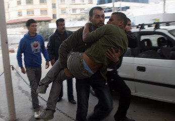 A Palestinian man carries a wounded youth into a hospital in Nablus