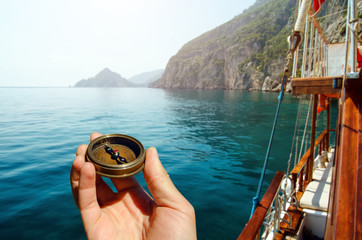 Hand holding old compass on wooden boat in the sea