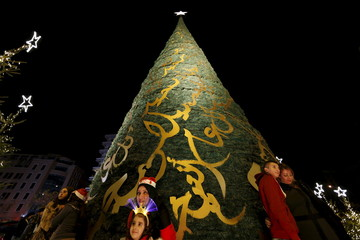 Residents take pictures in front of a decorated Christmas tree in Beirut