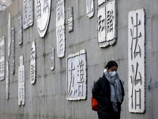 A woman wearing a protective mask walks past a wall of a school bearing educational slogans in Beijing