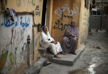 Palestinian women rest at the entrance of their house as they escape the heat during power cut at Shatti refugee camp in Gaza City