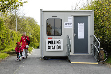 A woman and child pass a mobile polling station at Kingsnorth near Ashford