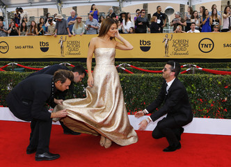 Television presenter Maria Menounos waits as assistants adjust her dress as she arrives at the 21st annual Screen Actors Guild Awards in Los Angeles