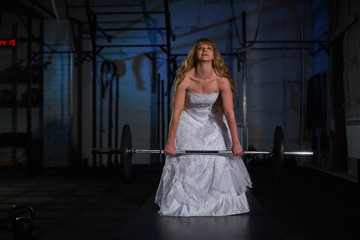Beautiful and muscular bride blonde in a wedding dress doing an exercise with a barbell in a gym, crossfit