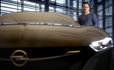 Kim, a South Korean designer for German car manufacturer Opel, poses for a photo next to the Monza concept sports car at Opel's headquarters in Ruesselsheim