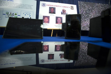 Photos of people arrested in a sting operation are reflected in a seized tablet computer following a news conference to announce the arrest of 71 individuals for sharing child pornography online in New York