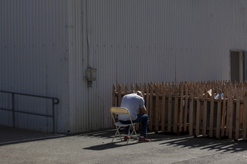 Tony Chavez holds his head in his hands after leaving his home due to the Valley Fire, at an evacuation center at the Napa County Fairgrounds in Calistoga, California