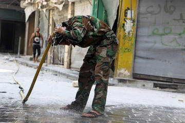A Free Syrian Army fighter washes his head in Old Aleppo, Syria