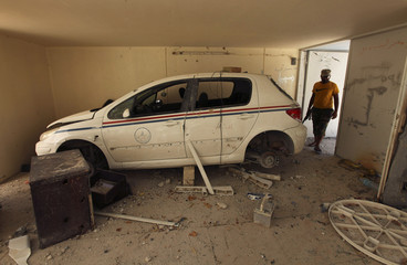 A man stands near a car destroyed by forces of Muammar Gaddafi in a residential area in Brega